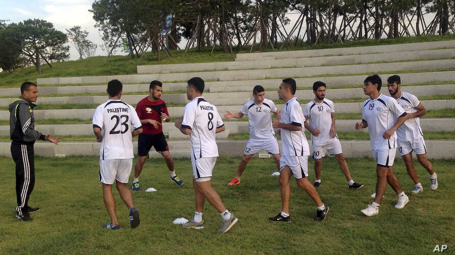 FILE - Palestinian football players warm-up during a training session at the Asian Games athletes' village in Incheon, South Korea.