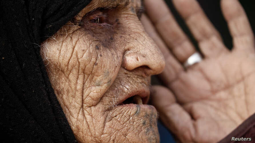 Khatla Ali Abdullah, 90, who recently fled her house in al-Mamoun district speaks with a Reuters journalist as she sits at her tent in Hammam al Alil camp, while Iraqi forces battle with Islamic State militants, in western Mosul, Iraq March 1, 2017.