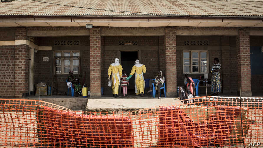 Medical workers lead a young girl with suspected Ebola into the unconfirmed Ebola patients ward run by The Alliance for International Medical Action (ALIMA), Aug. 12, 2018 in Beni, northeastern DRC.