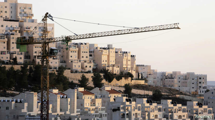 FILE - A crane is seen next to homes in the Har Homa Jewish settlement in Jerusalem.