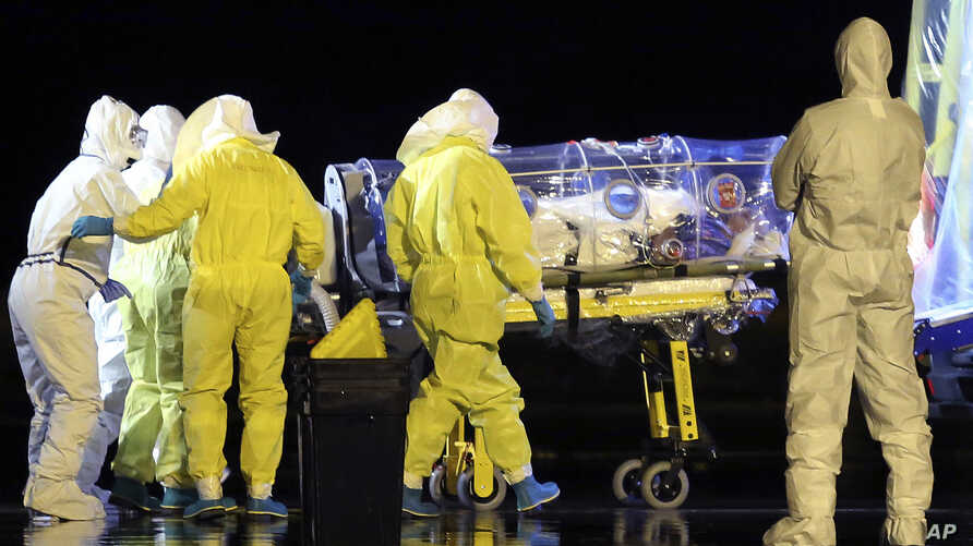 Aid workers and doctors transfer Manuel Garcia Viejo, a Spanish priest who was diagnosed with the Ebola virus while working in Sierra Leone, from a military plane to an ambulance as he leaves the Torrejon de Ardoz military airbase, near Madrid, Spain...