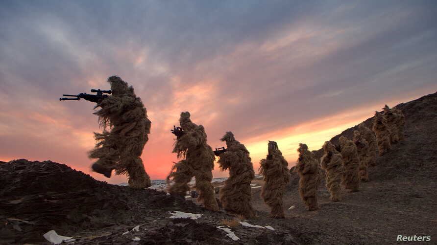 FILE - Soldiers of the People's Liberation Army (PLA) Marine Corps are seen in training at a military training base in Bayingol, Xinjiang Uighur Autonomous Region.