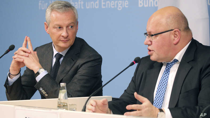 German Economy Minister Peter Altmaier, right, and France's Economy Minister Bruno Le Maire, left, address the media during a joint statement in Berlin, Germany, Feb. 19, 2019. (W. Kumm/dpa via AP)