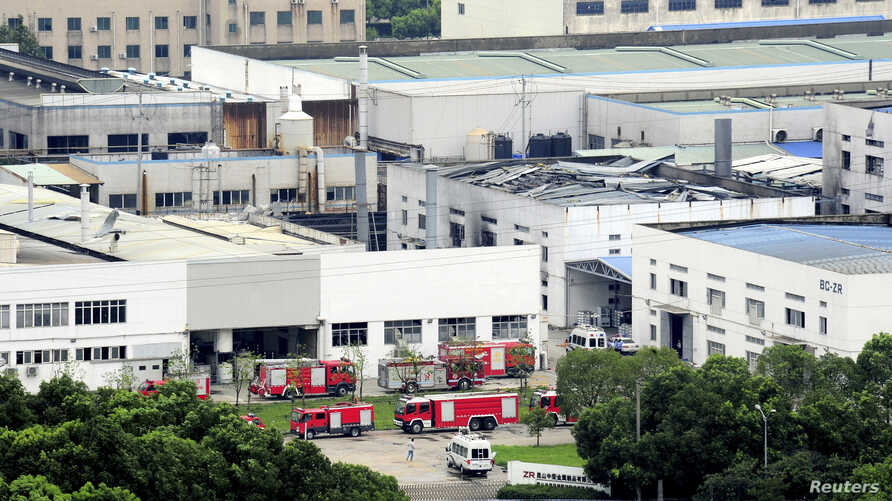 Firefighter trucks are seen next to a damaged building after an explosion at a factory in Zhoushan, Jiangsu province, China, Aug. 2, 2014.
