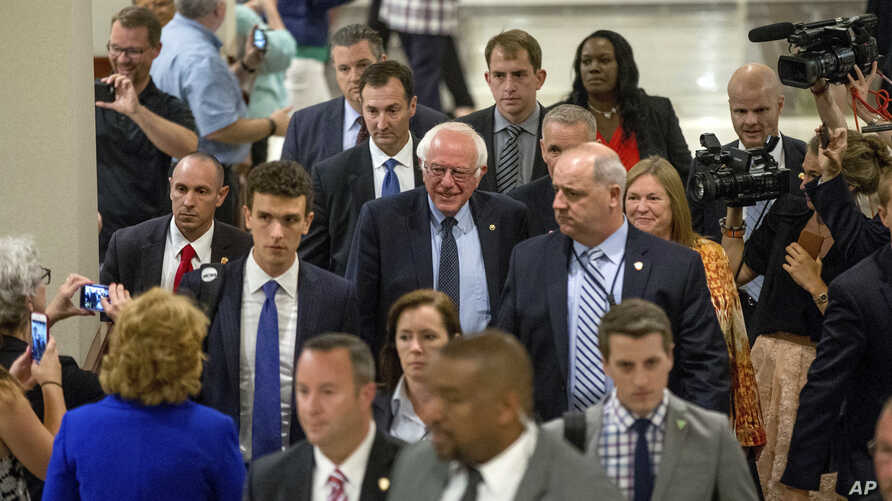 Democratic presidential candidate Sen. Bernie Sanders, I-Vt., accompanied by his wife Jane, right, leaves through the lobby of the Capitol Hilton after meeting with Democratic presidential candidate Hillary Clinton, in Washington, Tuesday, June 14, 2