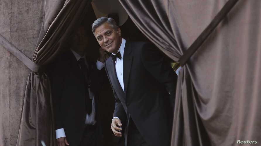 U.S. actor George Clooney smiles as he arrives by taxi boat to the venue of a gala dinner ahead of his official wedding ceremony in Venice, Italy, Sept. 27, 2014.