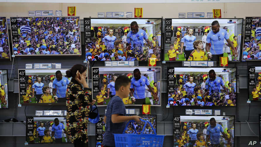 A woman and a child pass Chinese brands of flat screen TVs on display at a hypermarket in Beijing, July 11, 2018.