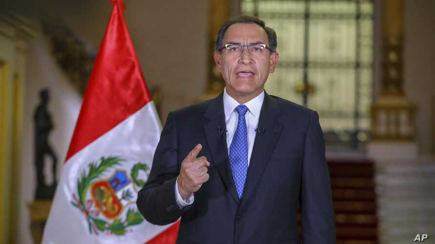 In this photo provided by the Peruvian government, President Martin Vizcarra delivers a national address from the government palace in Lima, Sept. 16, 2018.