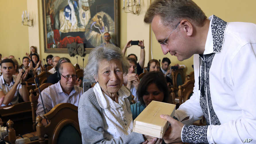 Lviv Mayor Andriy Sadoviy, right, presents a glass copy of an old metal synagogue key to Yanina Hescheles, Polish writer and a Nazi concentration camp survivor, at a ceremony commemorating the 75th anniversary of the annihilation of the city's Jewish