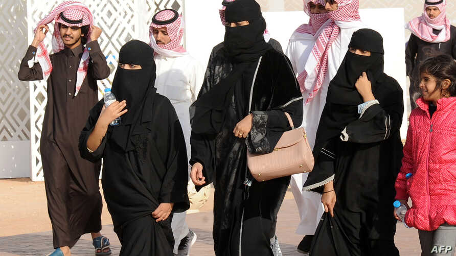 A picture taken on Jan. 19, 2018, shows Saudi women and men walking in Rumah, 160 kilometers east of Riyadh. For decades the religious police wielded unbridled powers as arbiters of morality, patrolling streets and malls to snare women wearing bright