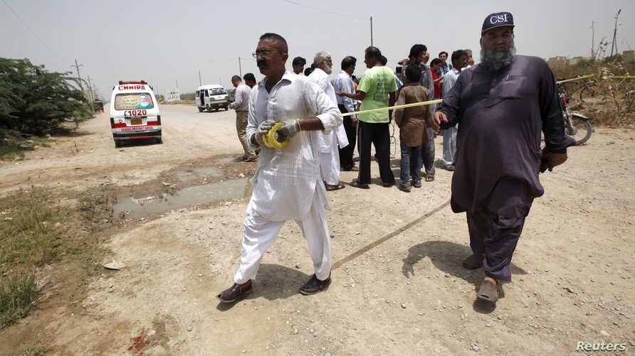 Security officials cordon off the area at the scene of an attack on a bus in Karachi, Pakistan, May 13, 2015. Gunmen on motorcycles opened fire on a bus in Pakistan's southern city of Karachi on Wednesday, killing at least 43 people, police said, in ...