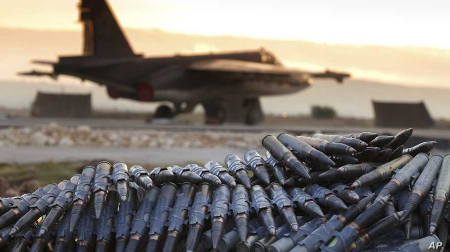 FILE - In a Dec. 18, 2015, photo, provided by the Russian Defense Ministry's Press Service, a load of ammunition is being prepared to be loaded onto a Russian war plane at Hmeymim air base, in Syria.