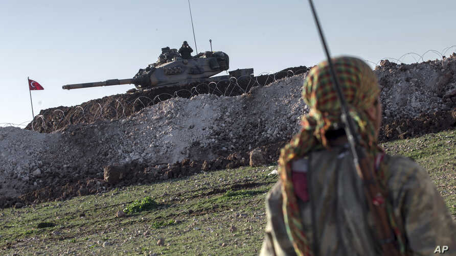 A Syrian Kurdish militia member of the YPG patrols near a Turkish army tank as Turks work to build a new Ottoman tomb in the background in Esme village in Aleppo province, Syria, Feb. 22, 2015.