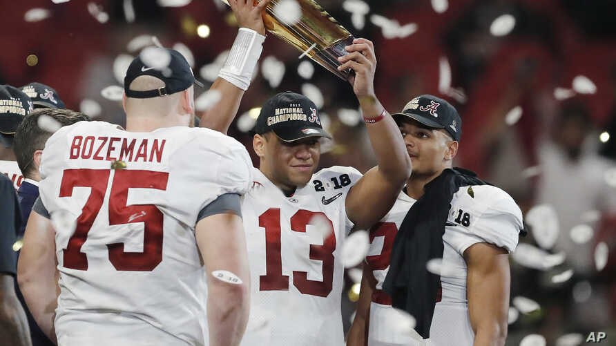 Alabama's Tua Tagovailoa holds up the championship trophy after overtime of the NCAA college football playoff championship game against Georgia Monday, Jan. 8, 2018, in Atlanta. Alabama won 26-23.
