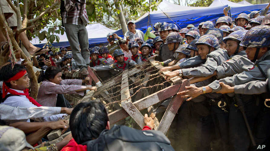 Student protesters struggle with riot police to remove a barricade installed by police during a protest ahead of a crackdown in Letpadan, 140 kilometers (90 miles) north of the country's main city Yangon, Myanmar Tuesday, March 10, 2015. Hundreds of