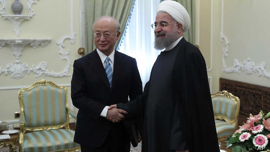 In this photo released by official website of the office of the Iranian Presidency, President Hassan Rouhani, right, and Director General of the International Atomic Energy Agency, IAEA, Yukiya Amano shake hands for media at the start of their meetin