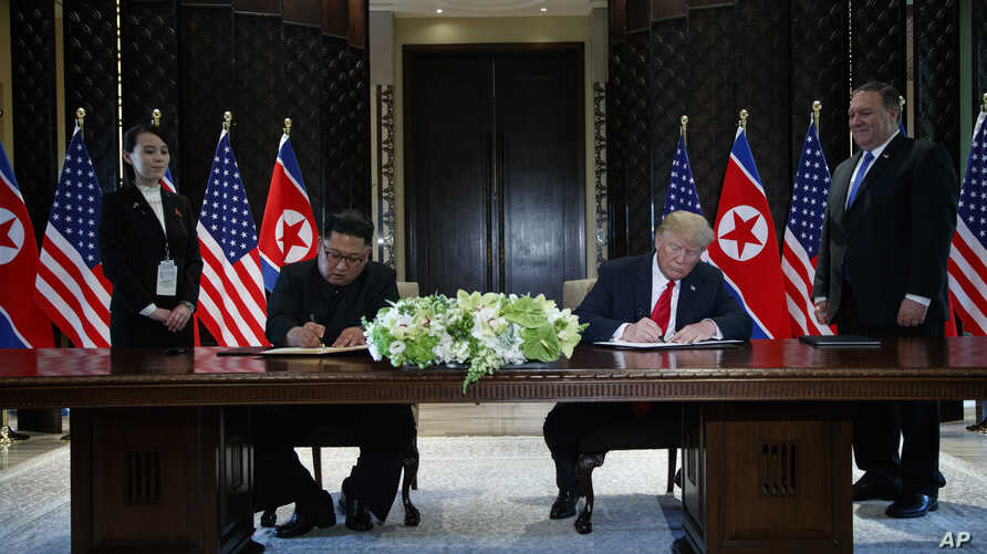 President Donald Trump and North Korean leader Kim Jong Un participate in a signing ceremony during a meeting on Sentosa Island, June 12, 2018, in Singapore.