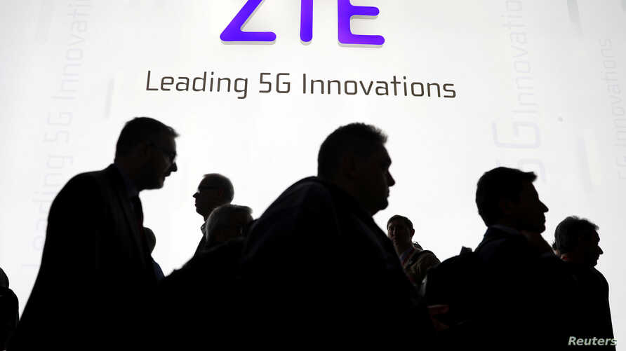 FILE - Visitors pass in front of the Chinese telecoms equipment group ZTE Corp booth at the Mobile World Congress in Barcelona, Spain, Feb. 26, 2018.
