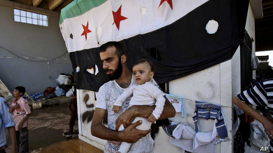A Syrian man, who fled his home due to government shelling, holds his son as they take refuge at Bab Al-Salameh crossing border, hoping to cross to one of the refugee camps in Turkey, near the Syrian town of Azaz, Sept. 12, 2012.