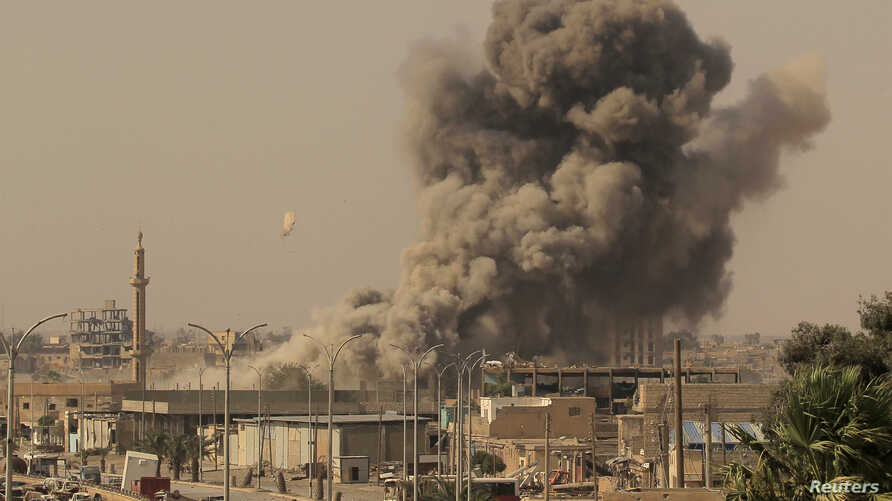 FILE - Smoke rises after an airstrike during fighting between members of the Syrian Democratic Forces and Islamic State militants in Raqqa, Syria, Aug. 15, 2017.