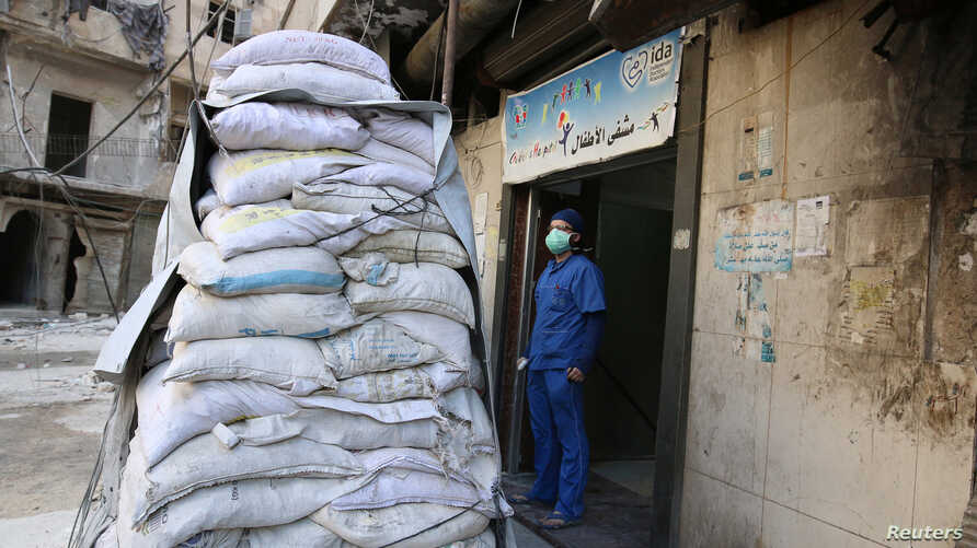 A medic stands behind sandbags in the damaged al-Hakeem hospital, in the rebel-held besieged area of Aleppo, Syria, Nov. 19, 2016. Top U.N.  officials warned Monday, Nov. 21, 2016, that health care services in Syria have been devastated by bombings.