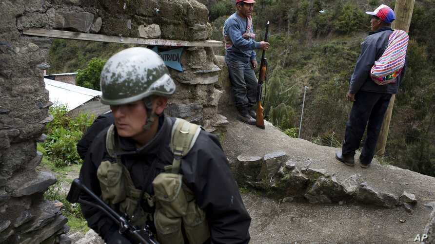 Self-defense members standing guard, top, talk as a soldier patrols outside a school that will be used as a polling station in Uchuraccay, Peru, April 9, 2016. Peruvians head to the ballot box for general elections on Sunday.