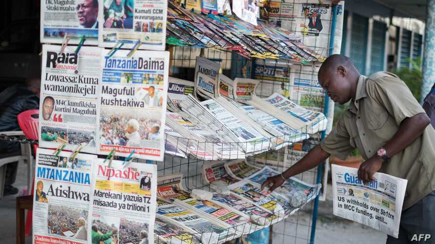 Newspaper vendor Julius Donald straightens newspapers at his stand in Mwanza, on September 19, 2015.