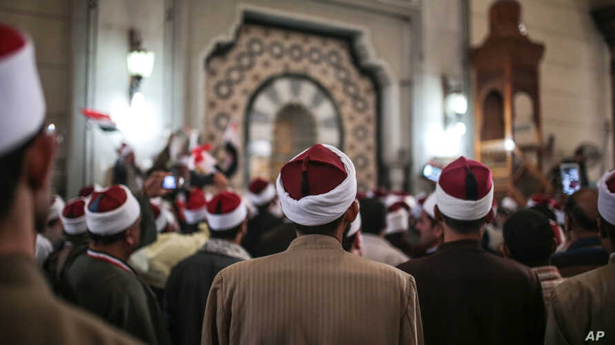 FILE - Muslim clerics are seen gathered at a mosque in central Cairo, Egypt, Feb. 3, 2015. Muslim clerics and scholars not in line with Islamic State postulates have been the latest target of IS propaganda videos.