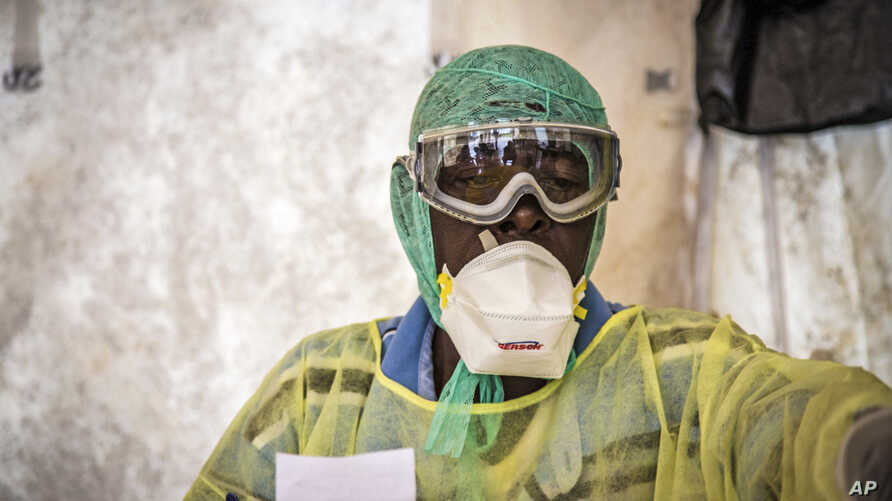 A health worker examines patients for Ebola inside a screening tent, at the Kenema Government Hospital about 300 km, (186 miles), from the capital city of Freetown in Kenema, Sierra Leone, Aug. 11, 2014.