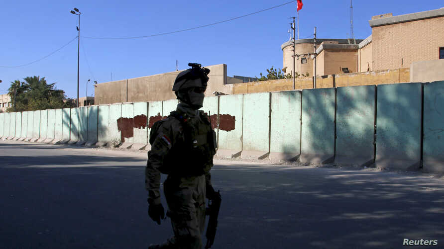 A member from Iraqi security forces walks past the Turkish embassy in Baghdad, Dec. 8, 2015.