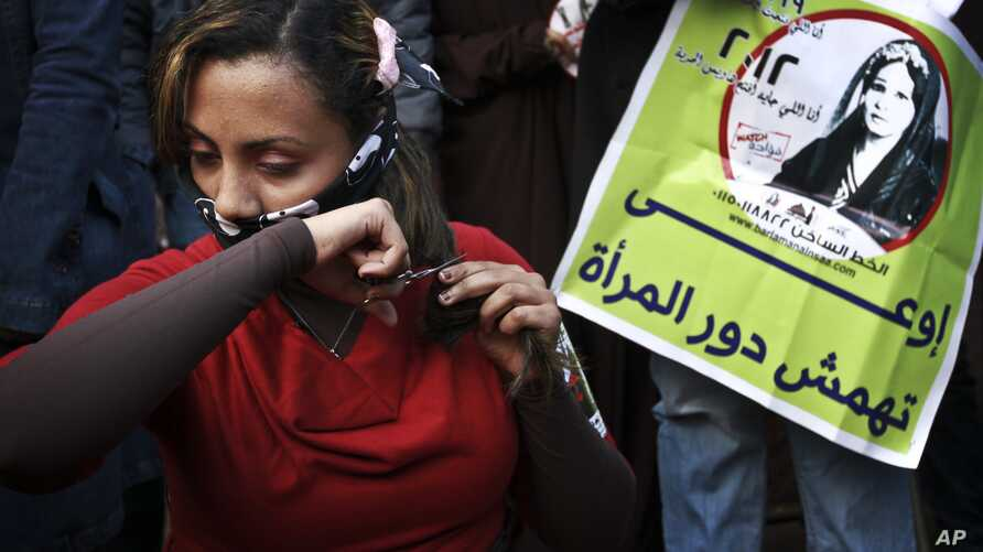 An Egyptian woman cuts her hair during a demonstration in Tahrir Square, Cairo, Egypt, Tuesday, Dec. 25, 2012.