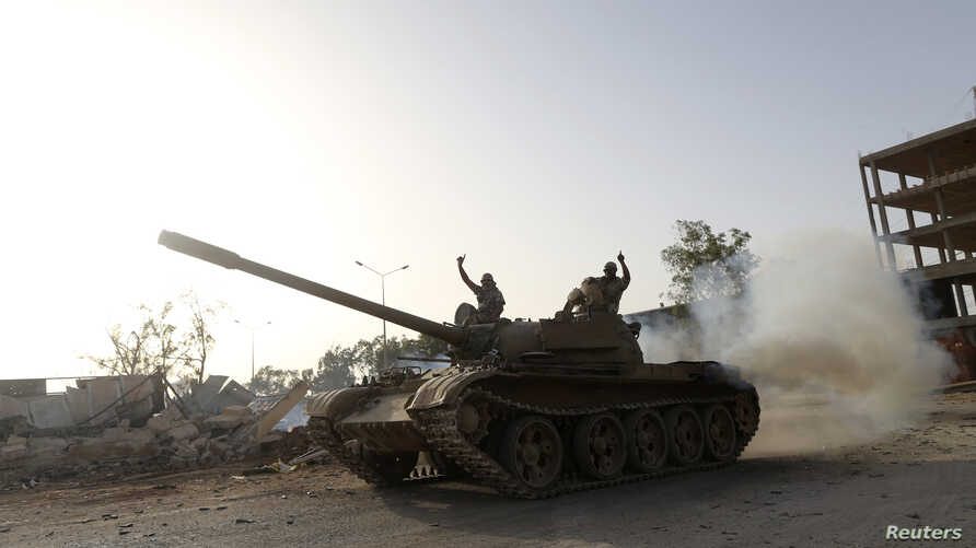 Fighters from the Benghazi Shura Council, which includes former rebels and militants from al-Qaida-linked Ansar al-Sharia, gesture on top of a tank next to the camp of the special forces in Benghazi, Libya, July 30, 2014.