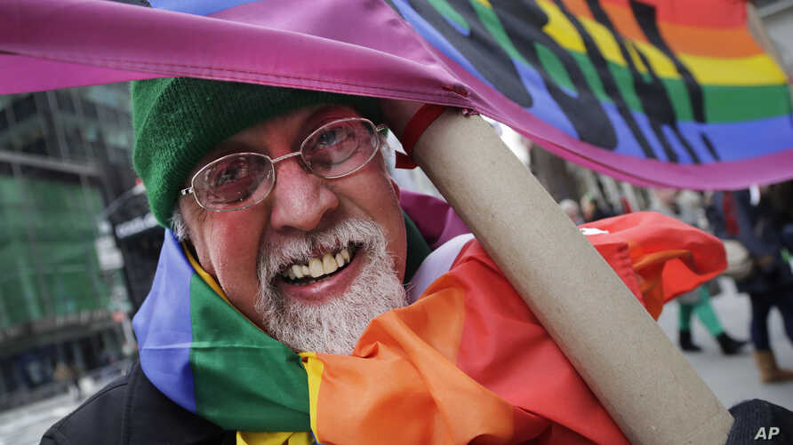 "FILE - Artist Gilbert Baker, designer of the Rainbow Flag, is draped with the flag while holding a banner that reads ""Boycott Homophobia"" before the start of the St. Patrick's Day parade in New York City, March 17, 2014."