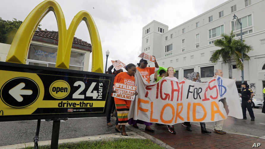 People protest for increased minimum wages outside a McDonald's restaurant in the Little Havana area in Miami, Florida, Dec. 4, 2014.