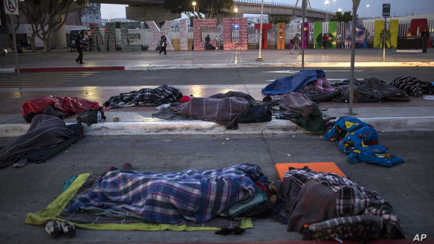 Migrants sleep on a street near the Chaparral border crossing in Tijuana, Mexico, Nov. 23, 2018.