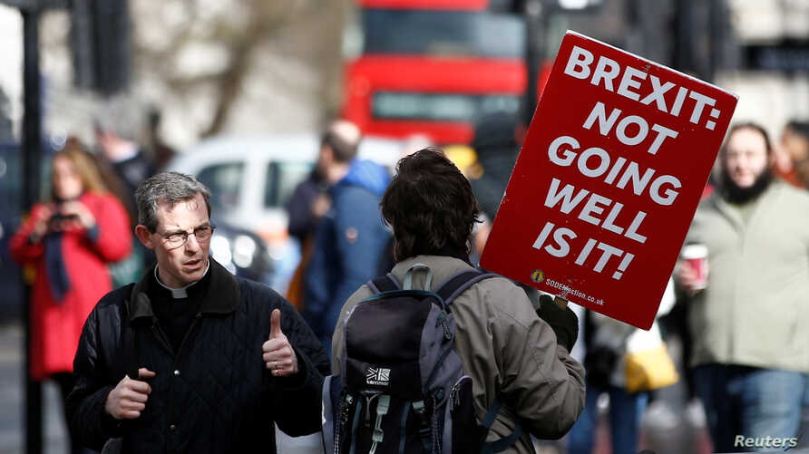 An anti-Brexit protester walks outside the Houses of Parliament in London, Britain, March 14, 2019.