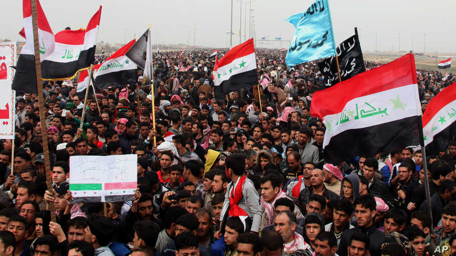 FILE - Sunni protesters chant slogans against the Iraq's Shiite-led government as they wave national flags during a 2013 demonstration in Fallujah.