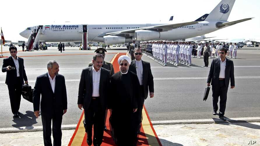 Iranian President Hassan Rouhani, center, walks with and Vice President Eshagh Jahangiri, center left, at Mehrabad airport in Tehran, Iran, Sept. 28, 2013.
