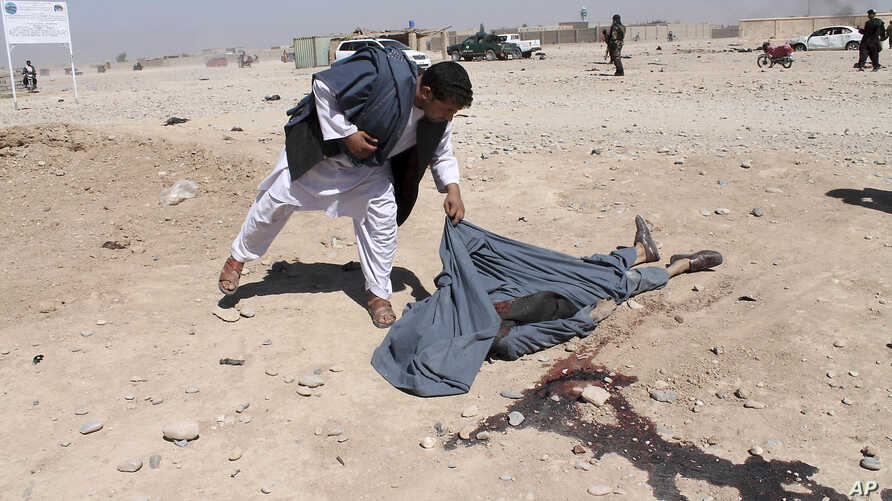 An Afghan man looks at the dead body of a victim of suicide attack in Lashkar Gah the capital of southern Helmand province of Afghanistan, Oct. 10, 2016.