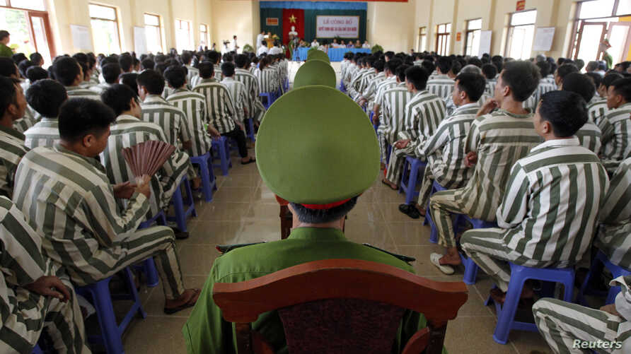 FILE - Policemen (center row) keep watch as inmates wait before being released from Hoang Tien prison, about 100 km (62 miles) outside Hanoi.