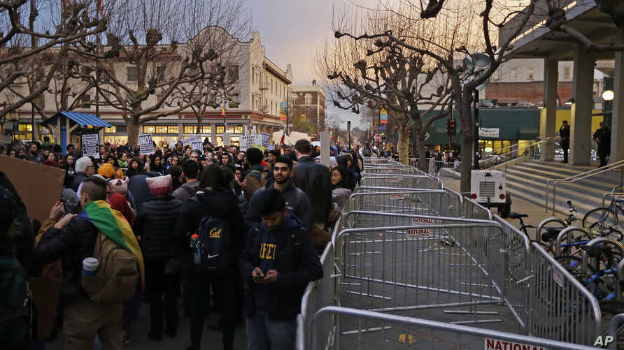 People protest the appearance of Breitbart News editor Milo Yiannopoulos, Feb. 1, 2017, in Berkeley, Calif. Yiannopoulos, a polarizing Breitbart News editor, is on the last stop of a tour aimed at defying what he calls an epidemic of political corre
