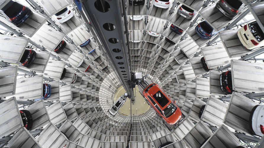 A VW Golf VII car (R) and a VW Passat are loaded in a delivery tower at the plant of German carmaker Volkswagen in Wolfsburg, March 3, 2015. Volkswagen will announce their results at their annual balance news conference on March 12 in Berlin. Picture