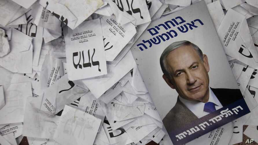 FILE - In this Wednesday, March 18, 2015 file photo, an election campaign poster with the image of Israeli Prime Minister Benjamin Netanyahu lies among ballot papers at his party's election headquarters, in Tel Aviv.