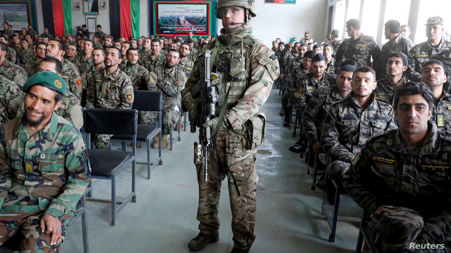 FILE PHOTO: Afghan National Army soldiers attend their graduation ceremony while a NATO soldier stands guard at the Kabul Military Training Centre in Kabul, Afghanistan Jan. 27, 2019.