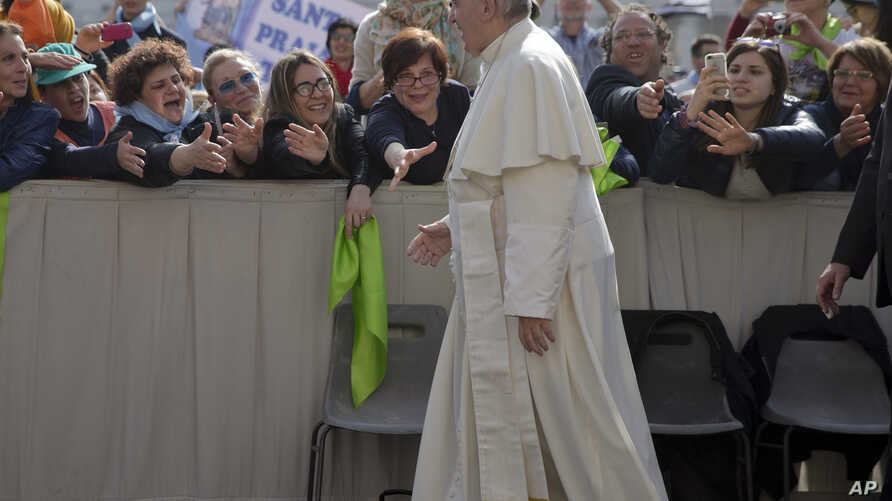 Faithful and tourists reach out to Pope Francis as he arrives for his weekly general audience, in St. Peter's Square at the Vatican, April 6, 2016.