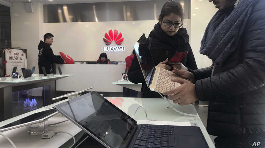 Foreigners look at a Huawei computer at a Huawei store in Beijing, China, Thursday, Dec. 6, 2018. Canadian authorities said Wednesday that they have arrested the chief financial officer of China's Huawei Technologies for possible extradition to the U