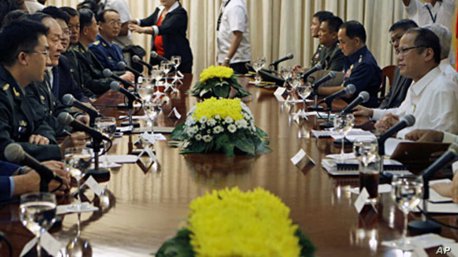 Philippine President Benigno Aquino III (R), talks with the delegation of Chinese Defense Minister Liang Guanglie, 2nd from left, during their meeting at the Presidential Malacanang palace in Manila, Philippines, May 23, 2011