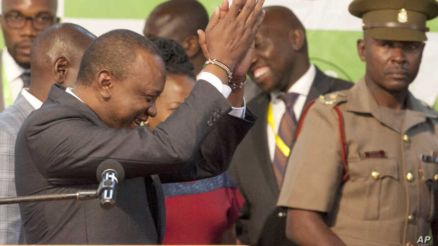 Uhuru Kenyatta, left, claps after he was announced the winner in the rerun of presidential election at the Centre in Bomas, Nairobi, Kenya, Oct. 30, 2017.