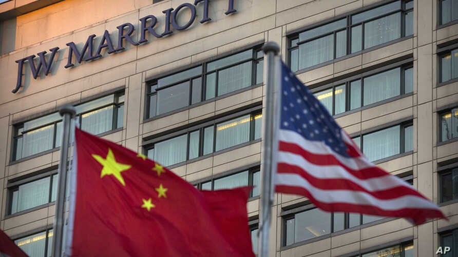 FILE - Chinese and American flags fly outside of a JW Marriott hotel in Beijing, Jan. 11, 2018.