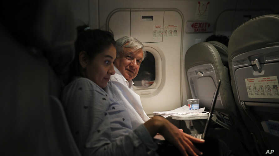 Mexican President Andres Manuel Lopez Obrador, center, sits with an assistant as he travels in economy class aboard a commercial flight from Guadalajara to Mexico City, Saturday, March 9, 2019.
